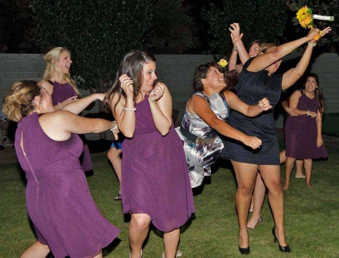 girls fighting for a bouquet at at a wedding