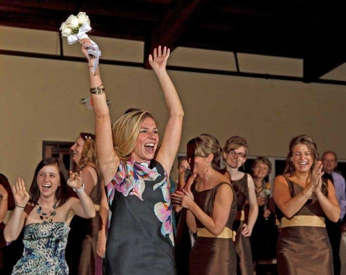 A woman celebrates catching the bouquet
