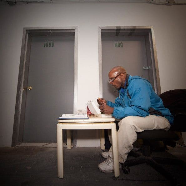 Gideon, a security guard of a storage company eats a simple dinner at work. Time: 7:42 PM  Location: Vinegar Hill, Brooklyn