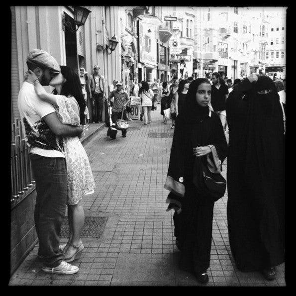 A young romantic couple kiss in Istanbul's shopping/tourist district as muslim women moves onto another shopping store. ©Thomas James Hurst 2011