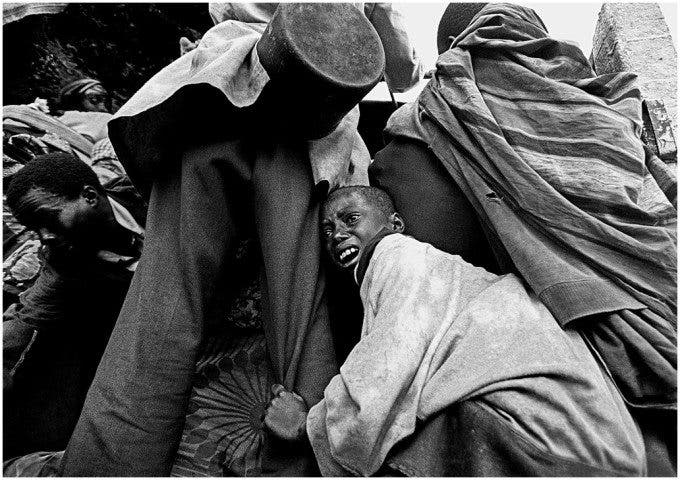 A boy is separated from his family in a chaotic scene where Rwandan's fearful of the coming darkness jumping in the back of trucks fleeing the fighting along the Rwandan-Zaire border. ©Thomas James Hurst - 1996 (World Press Photo - 1997)