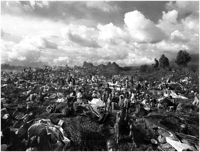Thousands upon thousands of exiled Rwandan's make camp along the roadside just inside the Rwandan boarder. Since the genocide in 1994 millions of Rwandan's have fled their homes and their country, but are now returning in mass. ©Thomas James Hurst - 1996 (World Press Photo - 1997)