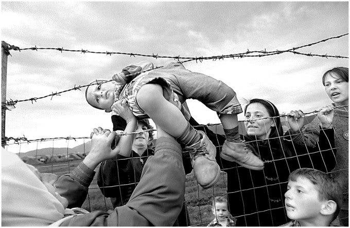 A baby is passed through the barbed wire of a family reuniting on the Albania-Kosovo boarder after fleeing the fighting between Kosovo Rebels and Serbian Soldiers. ©Thomas James Hurst - 1999