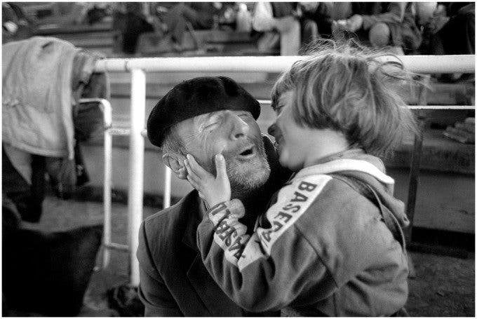 A grandfather and his granddaughter share smiles inside a high-school gym turned refugee center on the Albania boarder with Kosovo. ©Thomas James Hurst - 1999