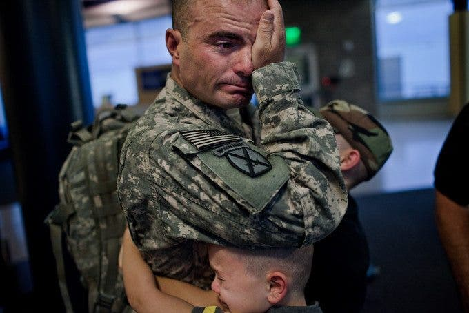 Sergeant First Class Brian Eisch weeps, as he struggles to say goodbye to his children.  (Photo by Marcus Yam)