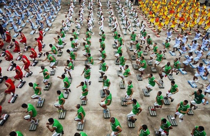 """Prisoners at Lurigancho Prison in Lima, Peru, known to be one of the most dangerous in the world, practice a sport called """"Full Body"""" for three hours on June 14, 2013, attempting to set the world record for the most people simultaneously performing the exercise, whether inside a jail or not. Prisoner Alejandro Nunez del Arco was a fitness instructor before he was convicted of kidnapping and sentenced to jail for 15 years. Late last year he started small workshops to teach other prisoners the sport, which combines elements of dance, Tae Bo and kick boxing. Little by little the sport became the pride of the prison. On the day this photo was taken about 1200 prisoners participated, each cell block donning a different color uniform. Full Body is a sport/fitness program that was founded by Peruvian Roger Romero, who also participated alongside the prisoners. They await confirmation of the record. Photo by Elie Gardner"""