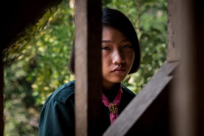 This girl waits outside her friend's house in the village of Ban Tha Ta Fang, while her friend is interviewed by the Children's Organisation of Southeast Asia (COSA) to corroborate reports that she is at risk of being trafficked.  Mickey Choothesa, CEO and Founder of COSA, says that, although COSA has had a direct impact on the lives of more than 1,000 girls, for every girl saved, another 20 slip through the cracks and are trafficked to work in the sex industry.