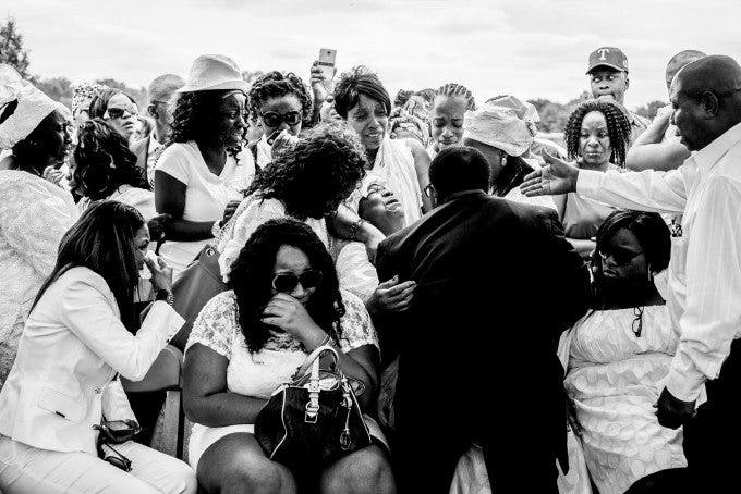 Family members weep as the casket of Alexander Kamara is lowered into the ground on Saturday, July 21, 2012. Kamara was a promising student and soccer player who was killed after being caught in the crossfire of a shooting that took place on a soccer field in Wilmington.