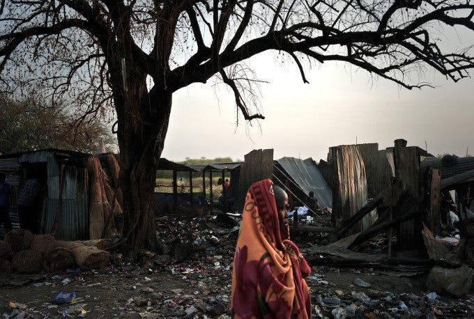 A woman walks along the destruction. People have very little money or none at all to flee the fighting and so must prepare for the continual conflict in their region.