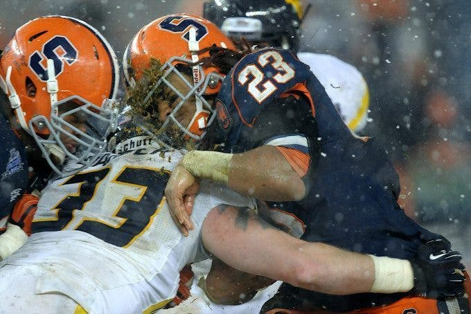 Syracuse Orange running back PRINCE-TYSON GULLEY (23) takes a big hit from West Virginia Mountaineers linebacker JARED BARBER (33) in the third quarter of the Pinstripe Bowl at Yankee Stadium in the Bronx, NY. Syracuse defeated West Virginia 38-14 to win the Pinstripe Bowl.