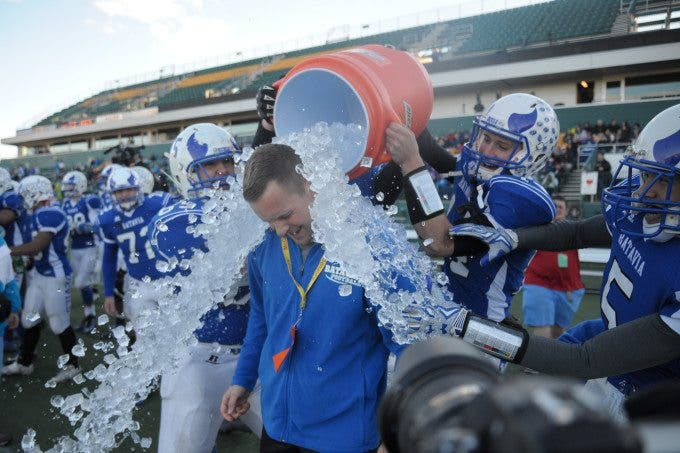 Batavia head coach Brennan Briggs (middle) gets the championship ice batch from players Nick Amico (65), Greg Mruczek (14), Eric Davis (5) and Clayton Gorski (74) following Batavia's 52-20 win over Livonia in the Section V Class B Championship game at Sahlen's Stadium in Rochester.