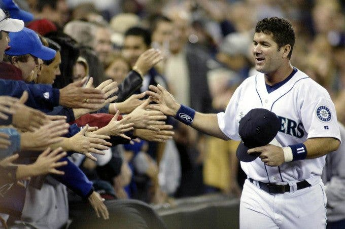 Seattle Mariners Edgar Martinez high fives Mariner fans as he runs the track surrounding the infield during Edgar Martinez Day on Saturday, Oct. 2, 2004 in Seattle. Jim Bryant Photo. All Rights Reserved