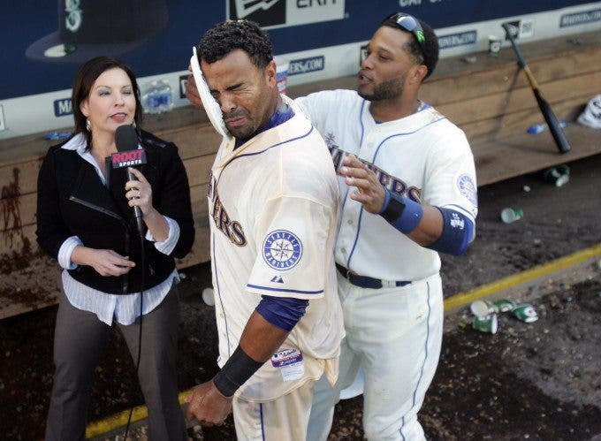 While be interviewed by Root TV's sports reporter, Jen Mueller, Seattle Mariners' Robinson Canto, right, hits Nelson Cruz with a plate of whipping cream after he hit a walk off home run to left field against the Texas Rangers' in the bottom of the 9th inning at SAFECO Field in Seattle on April 10, 2015. The Mariners came from behind to beat the Rangers 11-10. Jim Bryant Photo. ©2015. All Rights Reserved.