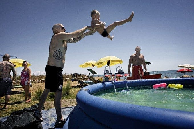 "Jamie, nick-named ""The Swan"", 31 years from London, throwing his friend's son in an inflatable pool. During a gathering between skinhead from all Europe in Roman seaside in august 2010. Jamie, soprannominato ""Il Cigno"", 31 anni e vive a Londra. Qui durante una festa estiva che riunisce Skinhead da diverse parti d'Europa nell'agosto del 2010. Qui Jamie gioca con il figlio di un amico, lanciandolo in una picina gonfiabile."