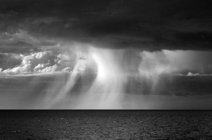 """'Cloud burst, Cardigan Bay' by Stuart Hall. 9th in the expert vote.  """"What a gorgeous study of elements this shot is. It mainly has 3 crucial areas. The bottom, the middle and the top. The dark bottom creates an intense contrast to the flowing middle and the deep dark top. It just looks stunning how the rain falls and flows through the center of the photo. The shot doesn't even need a boat or a subject. It stands out, because all the emptiness is filled with different tones and structures. So interesting!"""" - Marius Vieth."""