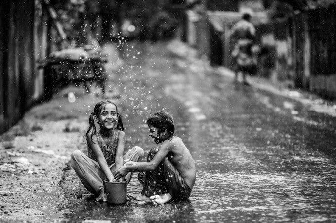 """'Monsoon Splash' by Ata Mohammad Adnan - 1st in the expert vote, 4th in the crowd vote. """"What a beautiful moment! It's so authentic, so real and full of emotions. The two kids playing with the water are so innocent in a way. It's so awesome to see how kids really don't mind the weather. Whether it's raining or the sun is out, they will always find a way to have a great time. I love the black and white post-processing and the open aperture. It really makes the subjects pop out. Keep up the great work!"""" - Marius Vieth"""