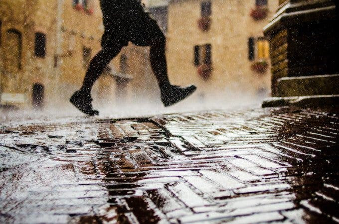 """'Running in Rain' by Jordan Rathkopf. 8th in the expert vote, 5th in the crowd vote.  """"Another killer example and execution of natural contrasts. It doesn't get better than this when it comes to that. The subject really comes out of the photo, although it's in the middle- to background of the frame. Positioning the subject in the top left really works well and makes the shot even more interesting. So beautiful to see how all the tiny rain drops are hitting the ground and how the water is flowing down to the left. Such a vivid moment!"""" - Marius Vieth"""