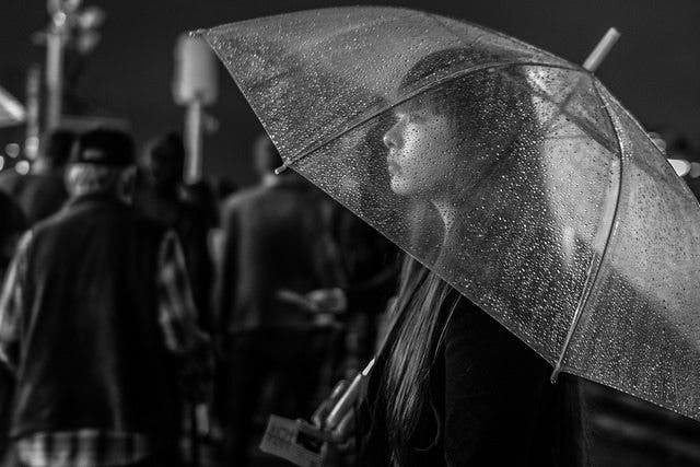 """'Umbrella Girl' by Iwona Pinkowicz. 6th in the expert vote.  """"Such a harmonic moment. It's so zen in a way. It feels like time froze for a moment even without the photo. Although there are slightly distracting elements in the background, the see-through umbrella covered in rain with the beautiful woman under it just makes up for a great subject. In addition, the composition really underlines the key elements in the photo. The black and white also works great. It reduces everything to its essence and brings out what's really important."""" - Marius Vieth"""