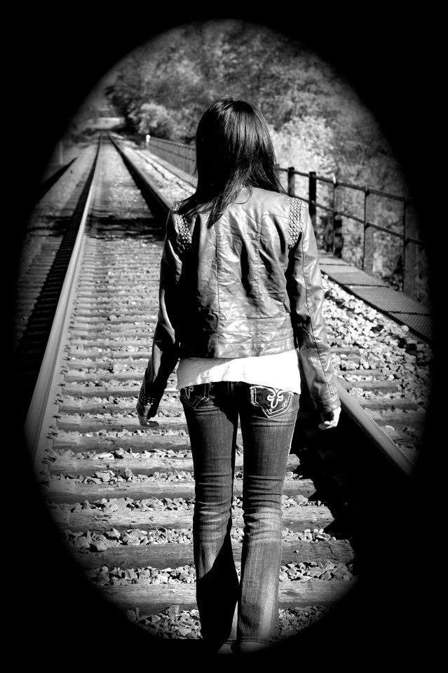 High school senior on railroad tracks. Photo by NAME REDACTED.