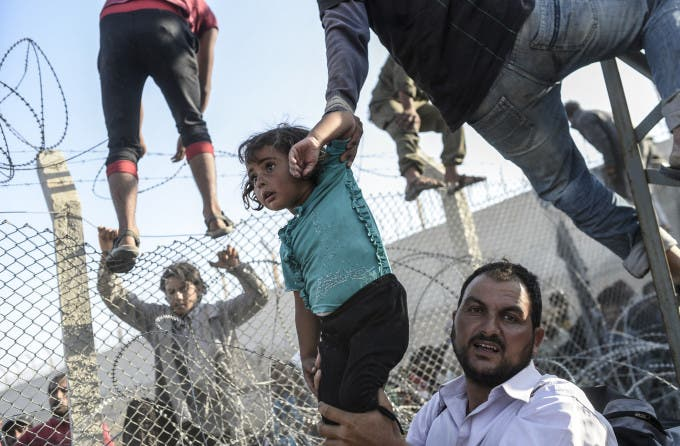 """A Syrian child fleeing the war is lifted over border fences to enter Turkish territory illegally, near the Turkish border crossing at Akcakale in Sanliurfa province on June 14, 2015. Turkey said it was taking measures to limit the flow of Syrian refugees onto its territory after an influx of thousands more over the last days due to fighting between Kurds and jihadists. Under an """"open-door"""" policy, Turkey has taken in 1.8 million Syrian refugees since the conflict in Syria erupted in 2011. AFP PHOTO / BULENT KILIC / AFP / BULENT KILIC"""