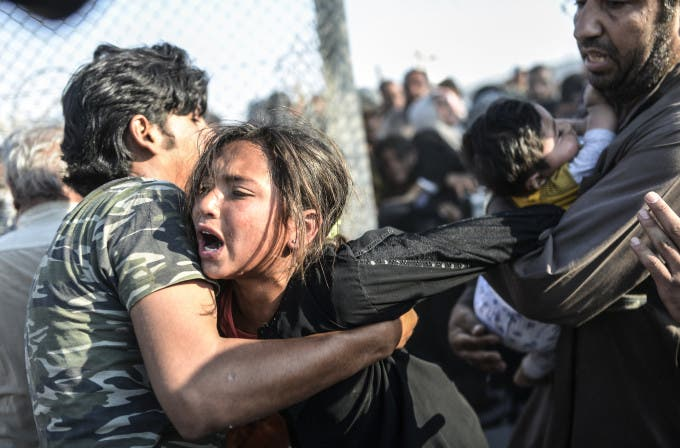"""Syrians fleeing the war rush through broken down border fences to enter Turkish territory illegally, near the Turkish border crossing at Akcakale in Sanliurfa province on June 14, 2015. Turkey said it was taking measures to limit the flow of Syrian refugees onto its territory after an influx of thousands more over the last days due to fighting between Kurds and jihadists. Under an """"open-door"""" policy, Turkey has taken in 1.8 million Syrian refugees since the conflict in Syria erupted in 2011. AFP PHOTO / BULENT KILIC / AFP / BULENT KILIC"""