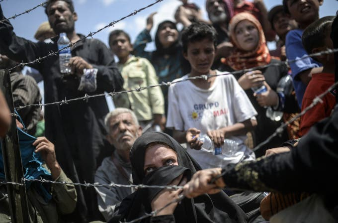 """Syrians fleeing the war wait to enter Turkey near the Turkish border crossing at Akcakale in Sanliurfa province on June 15, 2015. Turkey said it was taking measures to limit the flow of Syrian refugees onto its territory after an influx of thousands more over the last days due to fighting between Kurds and jihadists. Under an """"open-door"""" policy, Turkey has taken in 1.8 million Syrian refugees since the conflict in Syria erupted in 2011. AFP PHOTO / BULENT KILIC / AFP / BULENT KILIC"""