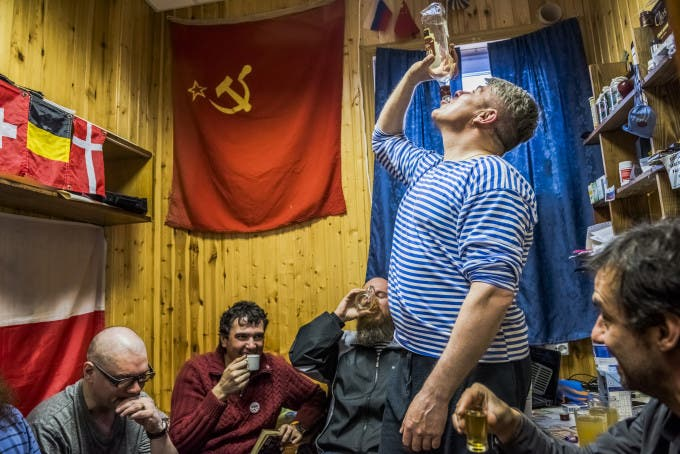 """7. ANTARCTICA - NOVEMBER 28, 2015: The winter expedition crew of Russian research team and (R) Chilean scientist Dr Ernesto Molina, drink """"Samagon"""" a home-made vodka, as they sit in a bedroom of the Bellingshausen Antarctica base on the 28th of November, 2015 near Villa Las Estrellas, in the Fildes Peninsula on King George Island, Antarctica. More than a century has passed since explorers raced to plant their flags at the bottom of the world. But today, an array of countries are rushing to assert greater influence in Antarctica. Russia built the continent's first Orthodox church, pictured here, on a glacier-filled island with fjords and elephant seals. Less than an hour away by snowmobile, Chinese labourers have updated the Great Wall Station, a linchpin in China's plan to operate 5 bases on Antarctica. And India's futuristic new Bharathi base resembles a spaceship. The continent is supposed to be protected as a scientific preserve for decades to come, but many are looking toward the day those protective treaties expire — and exploring the strategic and commercial opportunities that exist right now."""