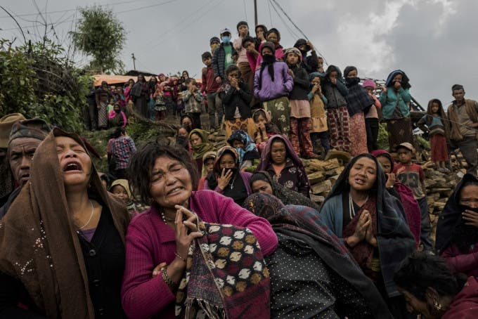 4—Gumda, Nepal. Friday, May 08, 2015: Bishnu Gurung (3L) weeps as the body of her daughter, Rejina Gurung, 3, (unseen), is recovered from the rubble of her earthquake destroyed home, on May 8, 2015 in the village of Gumda, Nepal. Neighbors discovered the body of the small girl in the collapsed entrance of the Gurung family home, ending a 13 day search for Rejina in the remote mountainous village of Gumda in Gorkha district. On the 25th of April, just before noon local time, as farmers were out in fields and people at home or work, a devastating earthquake struck Nepal, killing over 8,000 people and injuring more than 21,000 according to the United Nations Office for the Coordination of Humanitarian Affairs. Homes, buildings and temples in Kathmandu were destroyed in the 7.8 magnitude quake, which left over 2.8 million people homeless, but it was the mountainous districts away from the capital that were the hardest hit. Villagers pulled the bodies of their loved ones from the rubble by hand and the wails of grieving families echoed through the mountains, as mothers were left to bury their own children. Over the following weeks and months, villagers picked through ruins desperate to recover whatever personal possessions they could find and salvage any building materials that could be reused. Despite relief teams arriving from all over the world in the days after the quake hit, thousands of residents living in remote hillside villages were left to fend for themselves, as rescuers struggled to reach all those affected. Multiple aftershocks, widespread damage and fear kept tourists away from the country known for its searing Himalayan peaks, damaging a vital climbing and trekking industry and compounding the recovery effort in the face of a disaster from which the people of Nepal continue to battle to recover.