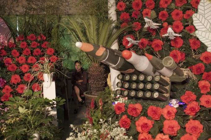 """A North Korean woman sits next to models of military weapons at a festival for the """"Kimilsungia"""" and """"Kimjongilia"""" flowers, named after the country's late leaders, in Pyongyang, North Korea, Wednesday, July 24, 2013. The exhibition was held to mark the 60th anniversary of the end of the Korean War on July 27."""