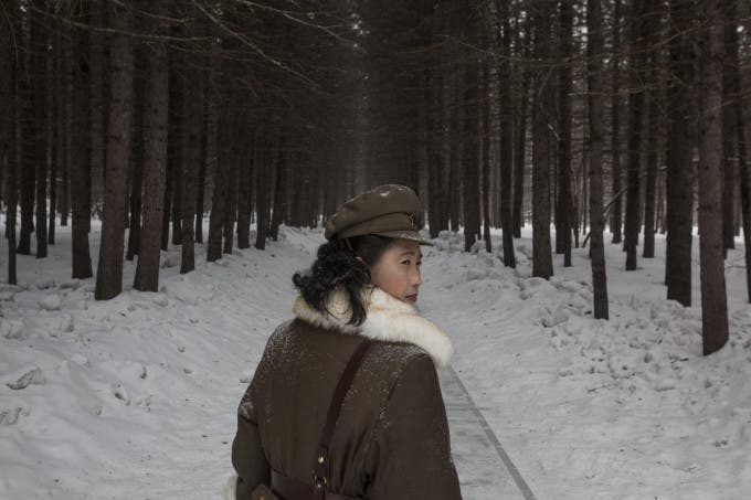 In this Wednesday, April 4, 2012 photo, a North Korean soldier, working as a guide, walks through a forest that is said to be a former camp site where the late North Korean leader Kim Il Sung overnight while leading a battle against the Japanese at the foot of Mount Paektu, North Korea.
