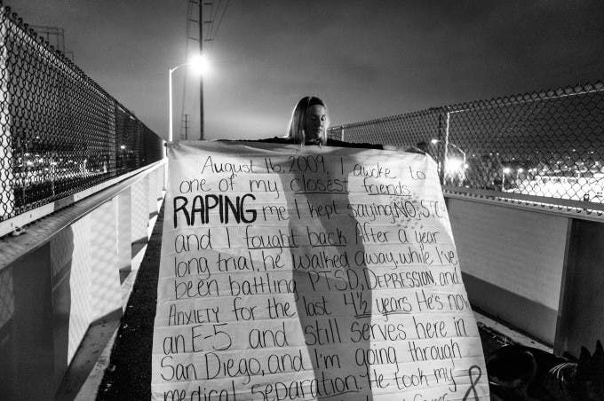 Under cover of darkness, US Navy sailor Melissa Bania, holds a banner inscribed with the story of her rape before hanging it on the footbridge across from Naval Station San Diego. Military Sexual Trauma survivors gathered in San Diego to bring attention to the epidemic of rape in America's military.