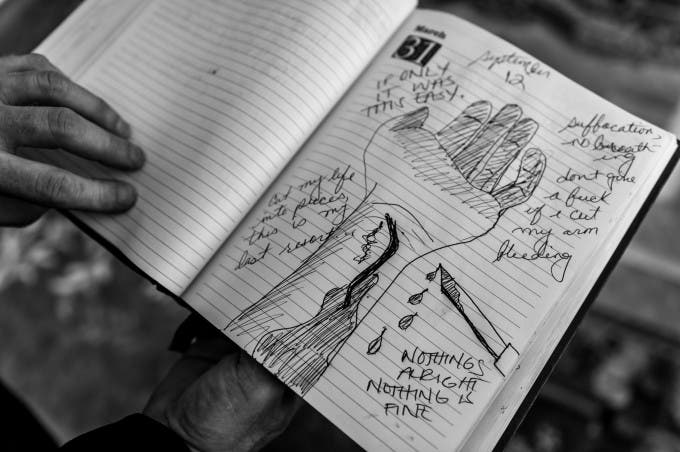 """Gary Noling holds his daughter Carrie's journal on the anniversary of her suicide in Alliance, Ohio. Carrie Goodwin suffered severe retaliation after reporting her rape to her US Marine commanders. Five days after she was went home with a bad conduct discharge, she drank herself to death. """"it destroyed my family. When Carrie died i lost all three of my kids and my grandkids. I lost two thirds of me. Two thirds of me is in that box of ashes."""" He did not know she had been raped until after her death."""