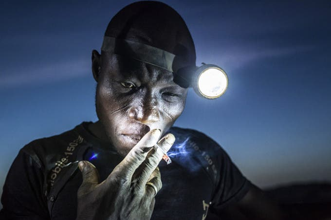 Arzuma Tindano (28) leads an eight-member crew of miners at Djuga, an artisanal mine in north-eastern Burkina Faso. They all trust him. They believe in his strength and his judgment. His 'office' is a 20 meters deep, narrow, dangerous and claustrophobic pit. The air there is thick, hot and humid with constant dust atacking his longs. He is just about to go into his pit again to do his night shift after he finishes his cigarete. Working in the night is better, he says, because the air is a bit cooler.