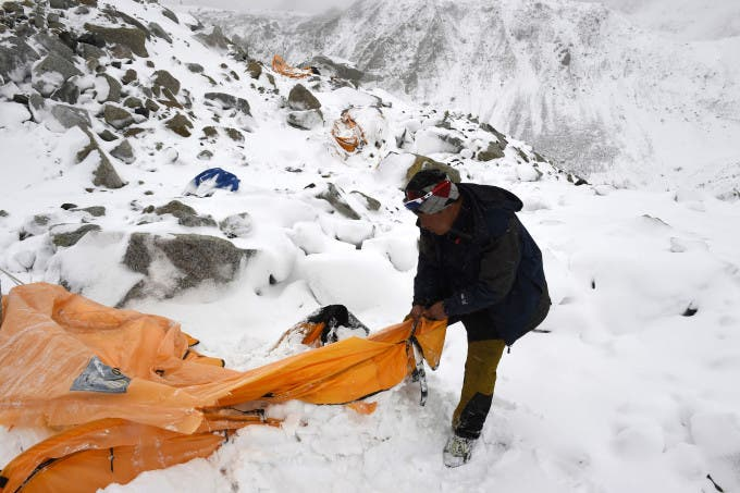 Trekking guide Pasang Sherpa searches for survivors among flattened tents moments after a wall of rock, snow and debris slammed on Everest base camp on April 25, 2015 killing at least 22 people. The avalanche was triggered by a powerful 7.8-magnitude earthquake that killed more than 8,000 people in the country. Rescue helicopters managed to reach the site about 18 hours after the avalanche as bad weather, aftershocks and fears of further avalanches rattled survivors. At the time of the disaster, the 5,364-meter-high Base Camp was teeming with hundreds of climbers and supporting teams who use the base to prepare their ascent to the peak of Mount Everest, the tallest mountain on Earth.