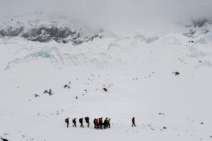 Rescuers carry an injured person to a medical tent moments after a wall of rock, snow and debris slammed into Everest Base Camp on April 25, 2015 killing at least 22 people. The avalanche was triggered by a powerful 7.8-magnitude earthquake that killed more than 8,000 people in the country. Rescue helicopters managed to reach the site about 18 hours after the avalanche as bad weather, aftershocks and fears of further avalanches rattled survivors. At the time of the disaster, the 5,364-meter-high Base Camp was teeming with hundreds of climbers and supporting teams who use the base to prepare their ascent to the peak of Mount Everest, the tallest mountain on Earth.