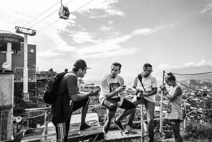 February 2015 - Rio de Janeiro, Brazil: Papo Reto collective members at Complexo do Alemao with a cableway station and cab in their back.