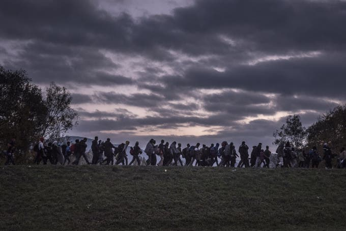 8 - Migrants walked atop a dike as Slovenian riot police escorted them to a registration camp outside Dobova. War, drought and more are driving millions of people from their homelands.