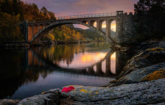 "500px Photo ID: 125762115 - I didnt really want to call it Skodje Brua, and it feels like something out of a fairytale, but couldnt think of a special one that it fit, so i thought I would leave it up to your imagination and decide which fairytale or bridge it reminds you of. For those that follow my profile I already posted a photo from here, but it is the other bridge as this one is part of two right after one another. The great grandfather of one of my friends was one of the ones that helped build this bridge and as a kid this was the regular bridge we used to get to the city. SCARY, expecially in the winter, you dont have a good view if there is another car coming on the other bridge as you go on. and there is pretty much place for one car as a time. and parts of it are on a slope, combined with ice can be scary. But now there is a large bridge just a hundred or two meters from this one that you can zoom by. While walking down the path down to here I noticed a 5 point leaf with great red colors, and so I took it along to put specifically in my composition in the name of Autumn. I did a bit more editing than im used to. but as a disclaimer most of the magical feeling is by making a HDR and darkening the whole as well as specific areas. and that was enough for most. I should have taken one more exposure for the sunlight but realised I didnt, so I had to paint out a bit of the white in the sky. added a bit of warmth to the sunset as well as selective vignetting. as well as about 15 images were used to make this. combined with HDR, long exposures, and Focus stacking to get the desired effect. especially when working with such small details. I dont know why, I love autumn and all the colors, But I dont feel as inspired to do nature photography and Feel more like ""Oh I guess I should take some photos of the season."" I like my results a lot there is something about it. cant quite wrap my brain around it. I hope yall enjoy it =D Feel Free to Share =D"