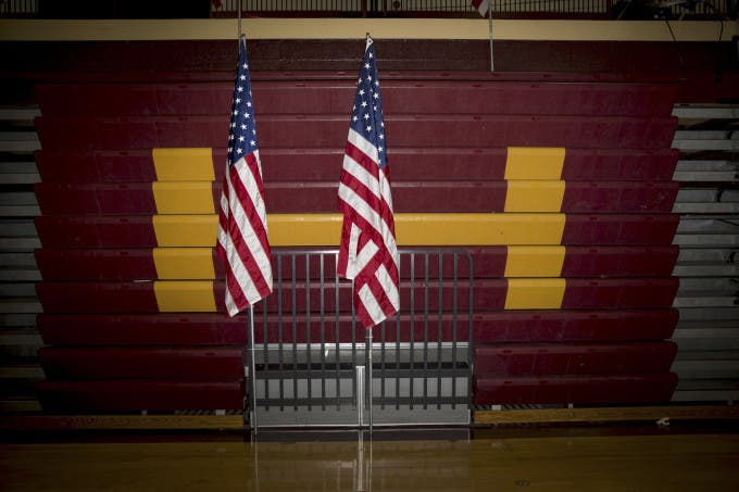U.S. flags stand in the gymnasium of Abraham Lincoln High School following a campaign event with Hillary Clinton, former Secretary of State and 2016 Democratic presidential candidate, in Des Moines, Iowa, U.S., on Sunday, Jan. 31, 2016. Photographer: Daniel Acker/Bloomberg