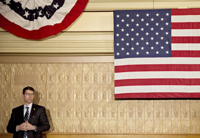 A U.S. Secret Service agent stands near an American flag ahead of an event with Hillary Clinton, former Secretary of State and 2016 Democratic presidential candidate, not pictured, in Decorah, Iowa, U.S., on Tuesday, Jan. 26, 2016. Photographer: Daniel Acker/Bloomberg