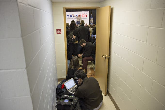 Members of the media work in a hallway as Senator Ted Cruz, a Republican from Texas and 2016 presidential candidate, speaks in the background during a town hall event in Salem, New Hampshire, U.S., on Friday, Feb. 5, 2016. Photographer: Daniel Acker/Bloomberg