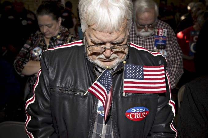 An attendee prays at the start of a campaign rally with Senator Ted Cruz, a Republican from Texas and 2016 presidential candidate, not pictured, at the Columbia Armory in Columbia, South Carolina, U.S., on Tuesday, Feb. 16, 2016. Photographer: Daniel Acker/Bloomberg