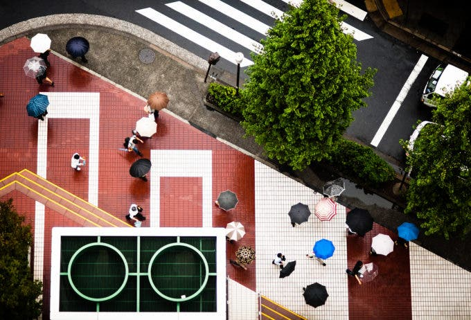Looking down at a geometric street scene on a rainy business day in the Ginza district of Tokyo, Japan. I took this by leaning out the window of a skyscraper.