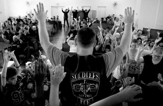 Photo by Christena Dowsett 1st Bikers Chruch pastor, Matthew Butler, leads the congregation in prayer during a Sunday morning service in Texarkana, Texas.