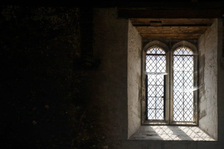 Hampton Court Palace's kitchens are located in a high-ceiling barn where the windows host spider webs. Made of iron framework, they leave beautiful geometric shadows on the walls and floor.